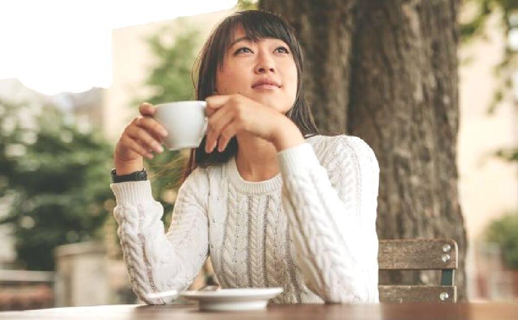 お茶を飲みながら空を見上げる女性