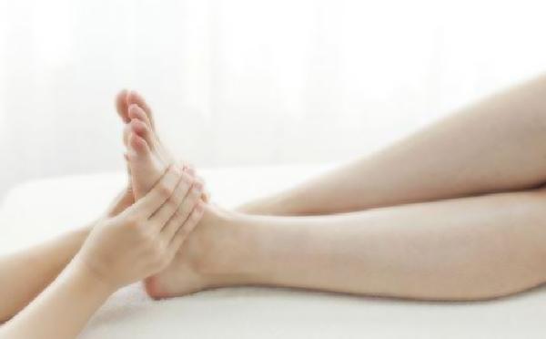 女性の足をマッサージ