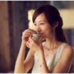 蓋椀のふたを押さえながら中国茶を飲む女性