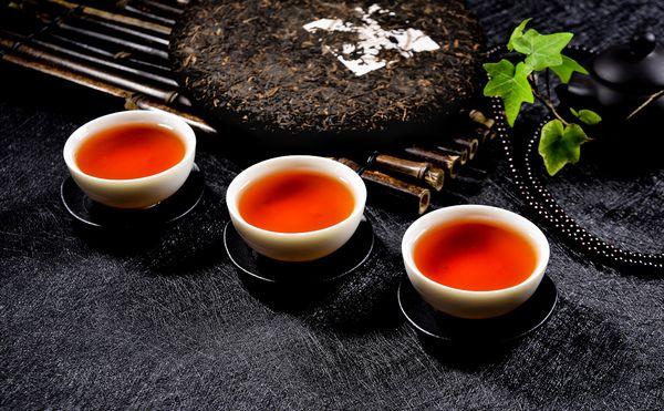 プーアル餅茶と3杯の茶杯に入ったプーアル茶の茶湯