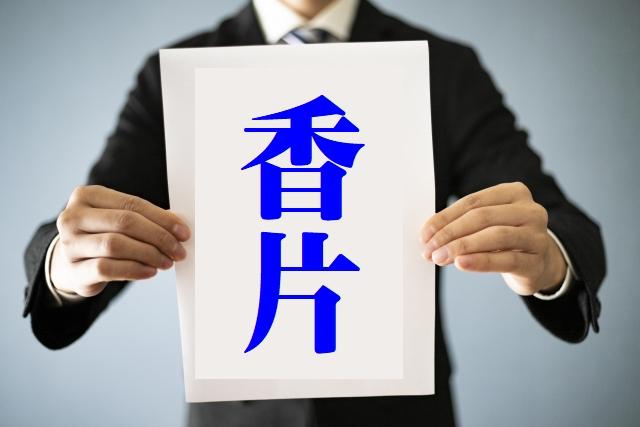 香片と書いた紙を持つ男性