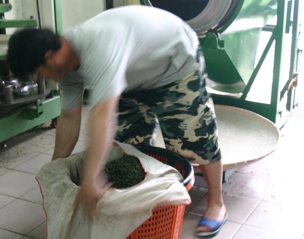 烏龍茶をシルクの布で包む男性