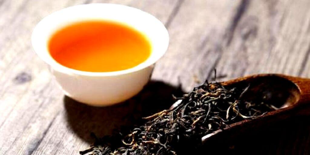 中国紅茶の湯に身に入った茶湯と置かれた紅茶の茶葉