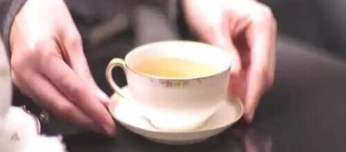 お茶のはいったティカップ差し出す女性の手 お茶のカフェインを考えるバナー